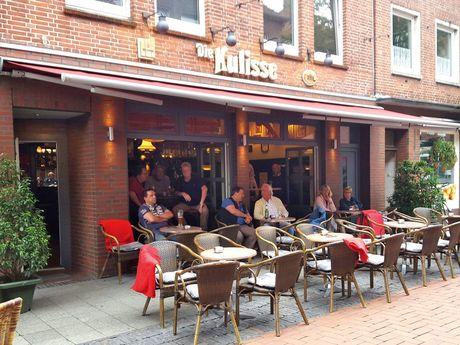 Zu sehen ist die Kulisse von außen mit einigen Tischen und Stühlen davor. Es sitzen einige Gäste dort.