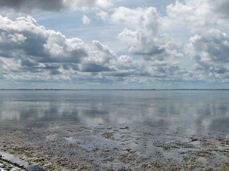 Weiter Blick auf das Wattenmeer, am Himmel grau-weiße Wolkenformationen.