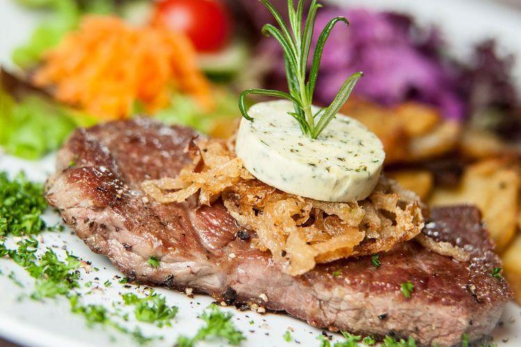 Zu sehen ist ein leckeres Stück Fleisch mit Kräuterbutter und im Hintergrund leicht verschwommen Salat. Das Bild steht als Beispiel für die vielen Leckereien, welche bei Emden a la Carte angeboten werden.