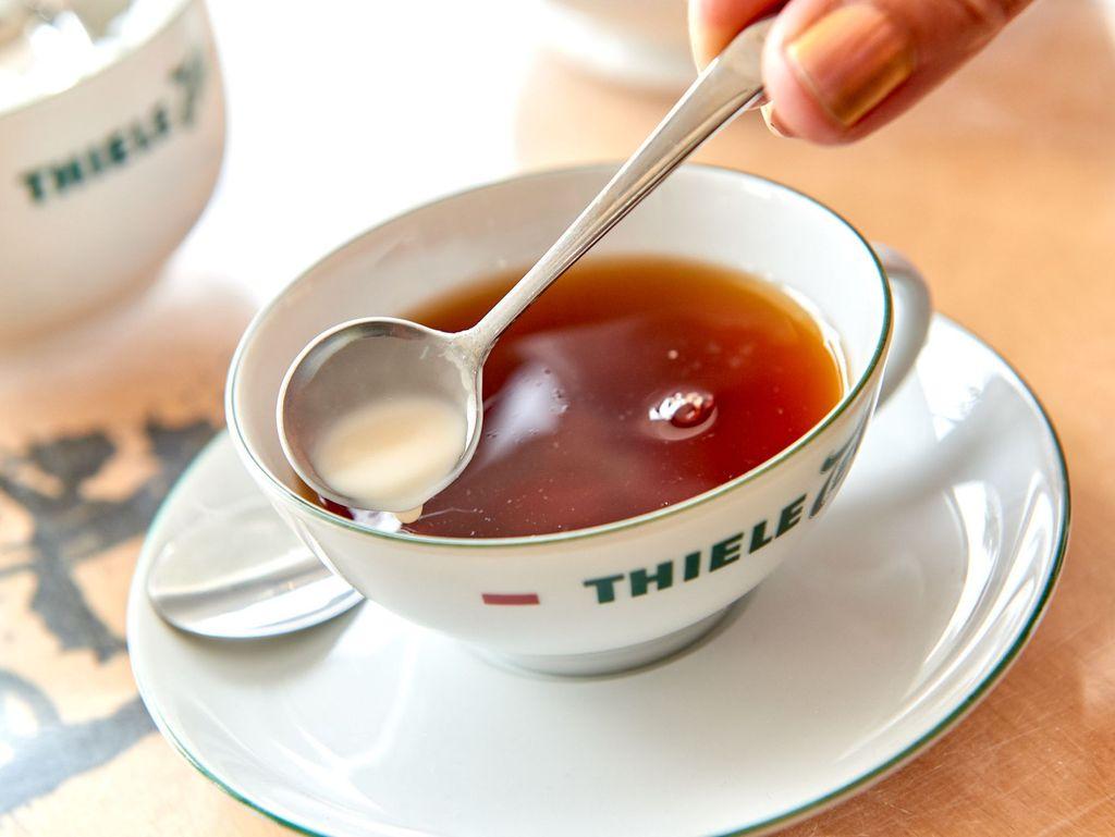 Nahaufnahme. Sahne wird nach ostfriesischer Tradition in eine Tasse mit Tee gefüllt