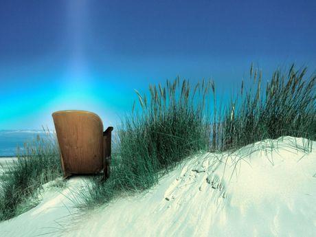 Ein alter Holzkinostuhl steht in den Dünen auf Sand zwischen Dünengräsern vor blauem Himmel. Ein kleines Stück Meer ist zu sehen.