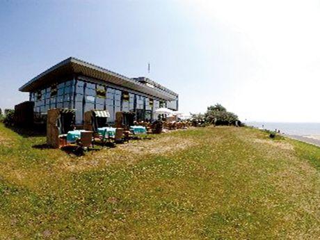 Zu sehen ist das Restaurant Strandlust, davor stehen Strandkörbe, Tische und Stühle