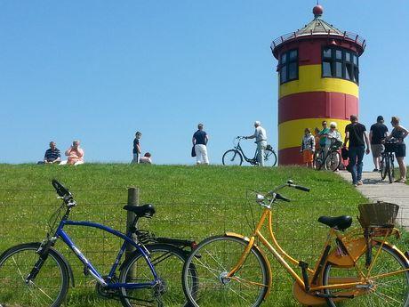 Der Pilsumer Leuchtturm unten vom Deich aus fotografiert. Im Vordergrund stehen 2 Fahrräder vor dem Deich und man sieht Mensche auf dem Deich und vor dem Leuchtturm