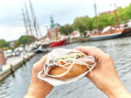 Ein Matjesbrötchen mit Zwiebelringen wird in 2 Händen gehalten. Im Hitnergrund erkennt man verschwommen den Delft mit Museumsschiffen und dem Ostfriesischen Landesmuseum