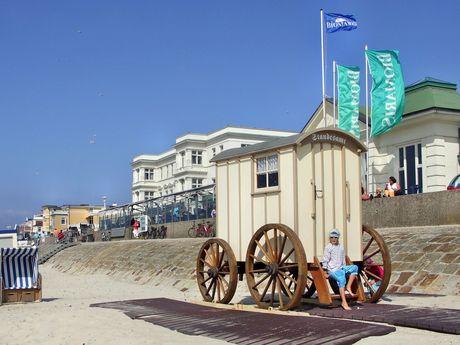 Zu sehen ist das Standesamt auf Norderney. Ein Badekarren, in welchem auch Trauungen stattfinden. Außerdem ein Strandkorb und Sandstrand.