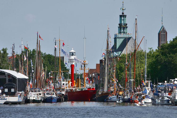 Festlich geschmückte Segelschiffe und das Feuerschiff im Delft. Eine Bühne ist aufgebaut und im Hintergrund ist das ostfriesische Landesmuseum zu sehen.