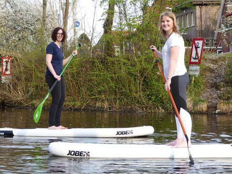 Zu sehen sind 2 junge Frauen jeweils auf einem Stand UP Paddling Brett