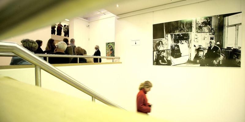 Sehr helle Aufnahme von der Kunsthalle von innen. Eine Person geht eine Treppe runter, eine Personengruppe im Hintergrund schaut sich Bilder an