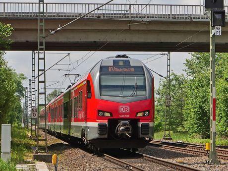 Zu sehen ist ein roter Regionalzug, welcher unter einer Brücke durch fährt.