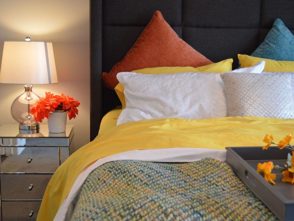Zu sehen ist ein Teil eines Bettes mit bunten Kissen, einem Teil eines Tabletts und ein Nachttischschrank mit Blumen
