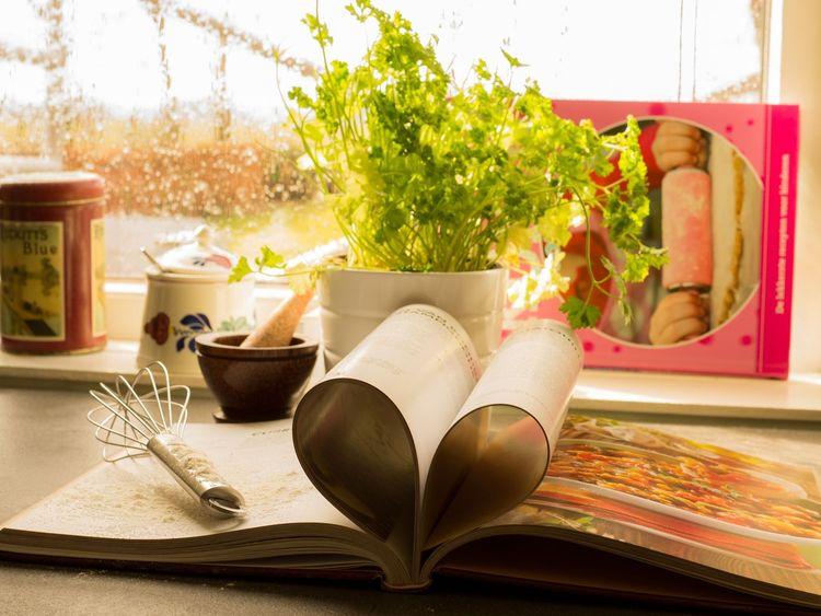 Auf einem Tisch liegt ein aufgeschlagenes Buch. In der Mitte sind einige Seiten zusammengesteckt und formen ein Herz. Im Hintergrund stehen Gewürze und man schaut aus einem Fenster.