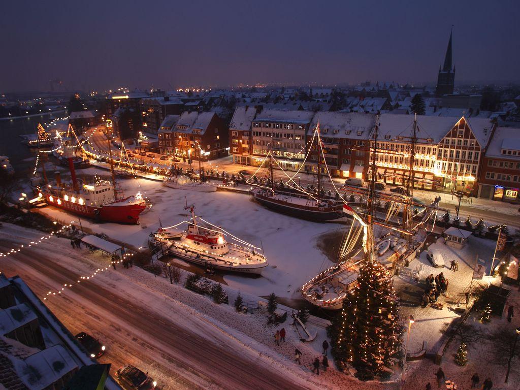 Blick von oben auf den leicht verschneiten Ratsdelft. Beleuchtete Museums und Segelschiffe liegen im Delft. Im Vordergrund steht ein beleuchteter Weihnachtsbaum.