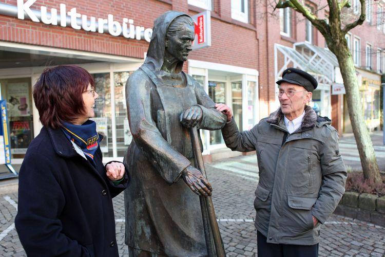 Eine Stadtführerin steht neben der Bronzefigur Peterke und erzählt einem interssierten Gast geschichtliches zu Emden
