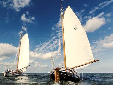 Zu sehen sind 2 Segelboote auf hoher See mit ihren weißen Segeln